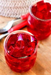 red jelly, cut into dice, inside two glasses of glass, on the table